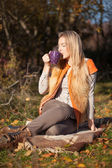Beautiful blond woman drinks tea in autumn foliage — Stock Photo