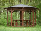 Brown wooden arbour at edge of forrest — Stock Photo