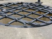 Latticed water well iron cover — Stock Photo