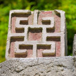 Ornamented decorating brick on wall against green — Stock Photo