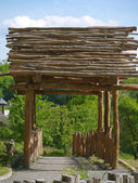 Gate with roof made from rough pecked wood — Stock Photo