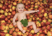 Cute baby on a pile o peaches — Stock Photo