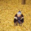 Baby on autumn leaves — Stockfoto
