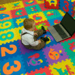 Stock Photo: Busy little baby working on computer in colorful playground mat