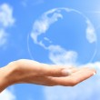 Globe in human hand against blue sky. Environmental protection c — Stock Photo