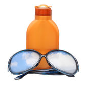 Plastic bottle for sun lotion and black sun glasses with blue sky reflecting, isolated on white. — Stock Photo