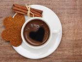 Cinnamon sticks, coffee cap and cookies on papyrus — Stock Photo