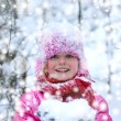 Stock Photo: Little girl in winter pink hat in snow forest.