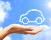 Hand with car against blue sky background — Stock Photo