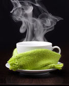 Coffee cup with smoke in green scarf — Stock Photo