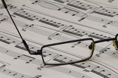 Glasses and music notes — Stock Photo
