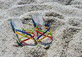 Woman's Flip, Colorful summer slippers on a quartz sand, beach, summertime, Pair of colorful slippers left in the sand with small stones — Stock Photo
