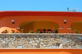Colorful typical sardinian house with the red flowers and blue sky background, orange house fragment close up in sunny day, colorful sardinian house, nice building in Porto Torres, Sardinia, Italy, — Stock Photo