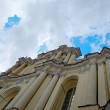 Vilnius,Lithuania.Vilnius University (the oldest university in Baltic states and one of the oldest in Eastern Europe).Vilnius University from unusual composition.Old church in dramatic sky background — Stock Photo