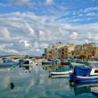 Malta Marsaxlokk village, native fishing boats luzzu, ancient fishing village, Mediterranean sea,blue sea and clouds formation, HDR photo, Marsaxlokk view,traditional colors of Malta,sunset time — Stock Photo