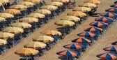沙滩遮阳伞,海滩伞天然砂背景上。用于阴影和灯的遮阳伞。五颜六色的遮阳伞和沙滩上的椅子。遮阳篷片段。夏季假期背景 — 图库照片