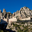 Montserrat Monastery is spectacularly Benedictine Abbey in the mountains near Barcelona, Catalonia,Spain.Montserrat.Panorama of the Monastery de Montserrat against background of mountains with shadows — Stock Photo #38341515