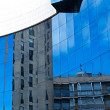 A modern colorful building mirror facade illuminated by the sun, blue sky reflected in modern building mirror glass wall, artistic and blur background photo. Reflections. Noisy photo — Stock Photo