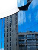 A modern colorful building mirror facade illuminated by the sun, blue sky reflected in modern building mirror glass wall, artistic and blur background photo. Reflections. Noisy photo — Stok fotoğraf