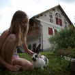 Teenage girl caressing rabbit in front of house — Vídeo de stock #28346409