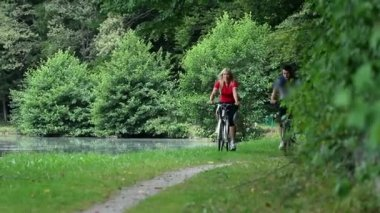 Young couple cycling in nature near the lake towards camera — Stock Video