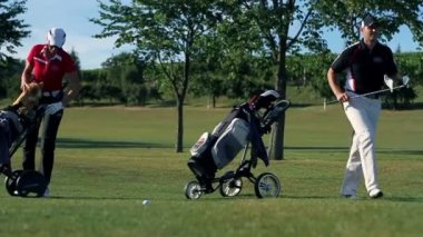 Shot of a couple coming to golf course carring all the golf equipment and preparing for hits — Stock Video