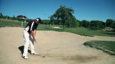 Shot of a man golfer on a sand golf course practising hits — Stock Video