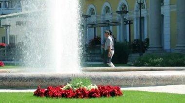 Skott av ett par promenader av fontänen i park — Stockvideo