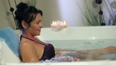 Mulher bonita e relaxante na jacuzzi com água quente e chapagne — Vídeo Stock