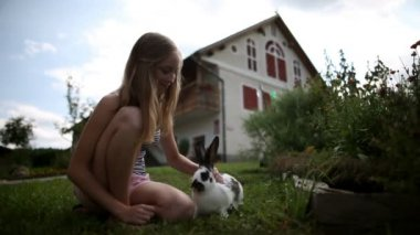 Teenage girl caressing rabbit in front of the house — Stock Video
