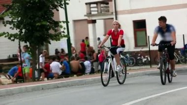 Young couple cycling through the town and passing volleyball game — Vídeo de stock