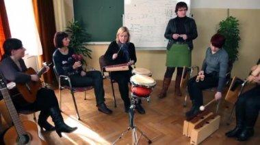 Da destra a sinistra pan colpo del gruppo di persone che stanno imparando una nuova canzone — Video Stock