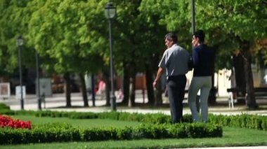Foto do parque em um par com hotel na parte de trás — Vídeo Stock