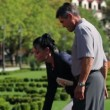 Senior couple enjoying free time in the park and gathering beautiful flowers — Stock Video