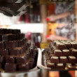 Stock Video: Shot of women looking at chocolate pralines in shot with reflection on showcase