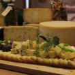 Close up of a man's hand picking served cheese from board — Stock Video #28352049