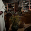 Stock Video: Monk walking in old store with herbs