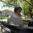 Shot of a couple sitting on a park bench on a beuatiful summer day — Stock Video