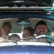 Stock Video: Family having fun on road towars summer holiday in very small car