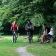 Young couple cycling in nature and passing family that sits on bench — Vidéo #28356339