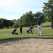 Shot of a couple on a sand golf course carring all the golf equipment and practising hits — Stock Video