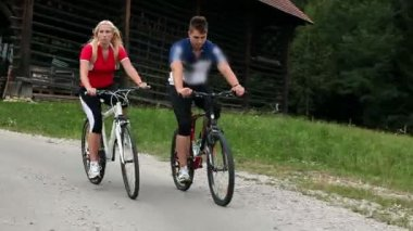 Young couple cycling in the countryside — Vídeo de stock