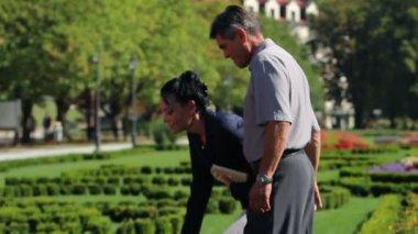 Kilka starszych korzystających z wolnego czasu w parku i zebranie piękne kwiaty — Wideo stockowe