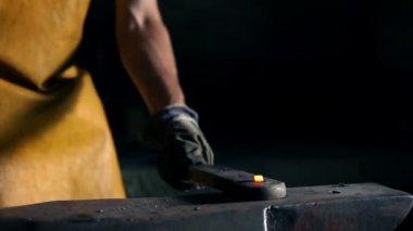 Close up slide shot of blacksmith who shapes metal into final shape — Stock Video