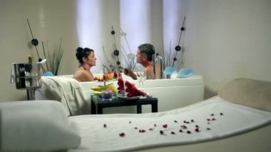 Shot of an older couple in jacuzzi eating fruits — Stock Video