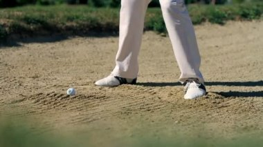 Shot of a man golfer on a sand golf course hitting the white golf ball — Stock Video