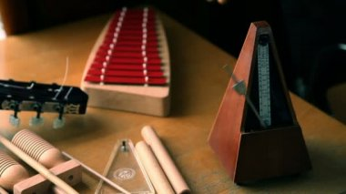 Close shot of a working metronome and anonymous hands that playing on xylophone — Stock Video