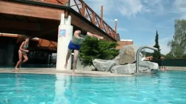 Young man jumping into a thermal pool — Stock Video