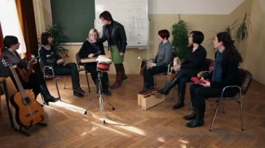 Right to left pan shot of the group of people that are learning a new song — Stock Video