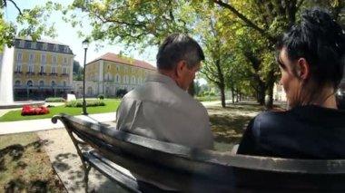 Foto de um casal sentado num banco de parque em beuatiful um dia de verão — Vídeo Stock